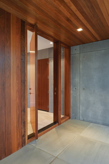 A mahogany front door, flanked by sidelites, welcomes guests. © Anice Hoachlander
