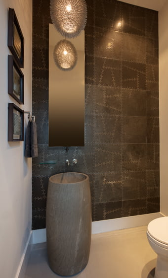 In the powder room, ceramic wall tiles with random metal insets mimic stones. © Geoffrey Hodgdon