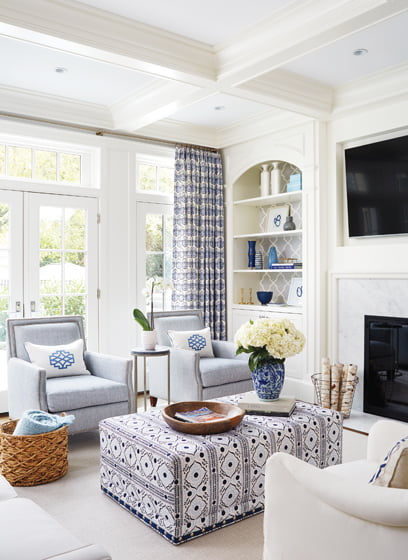 In the great room, coffered ceilings and built-ins add interest, as do graphic John Robshaw textiles.