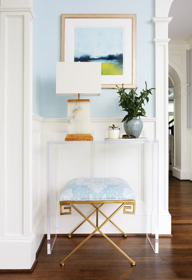 In the foyer, a gold-finished stool in Quadrille fabric tucks beneath a Lucite console.