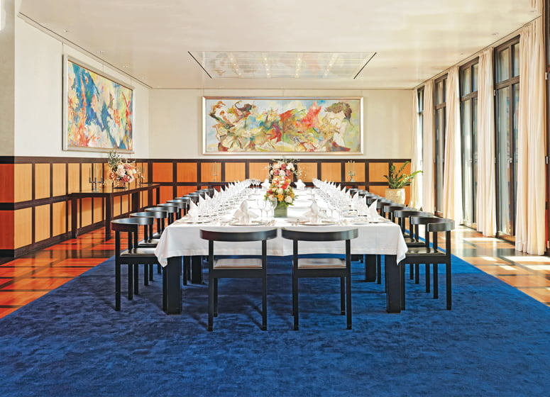 In the grand dining room, paintings by Bernard Schultze hang above chest-high wall panels.