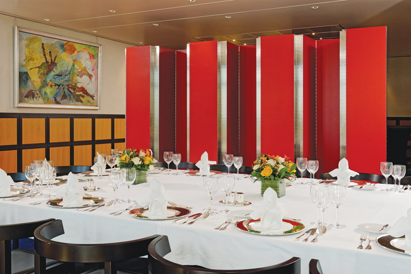 One leg of the L-shaped room can be partitioned off by a red-lacquered folding screen.