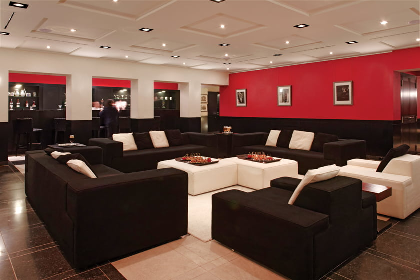 Red walls and dark woodwork and furniture conjure the feel of a German cabaret.