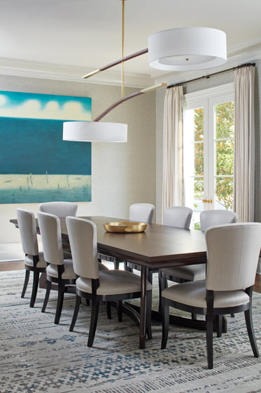 Zimmer + Rohde fabric covers the dining room walls; the chandelier is from Hudson Furniture.