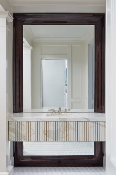 The vanities have drawers fronted in marble-and-brass inlay.