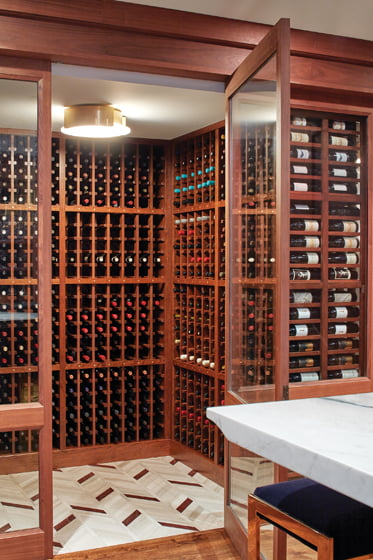 The wine cellar features a Waterworks marble-mosaic tile floor.