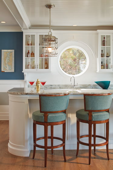 A porthole window and shades of blue-green convey a nautical vibe in the bar area.