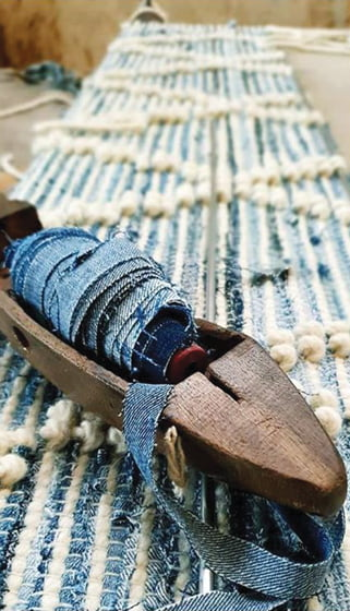 Strips of jeans are wound onto spindles before being spun on looms.