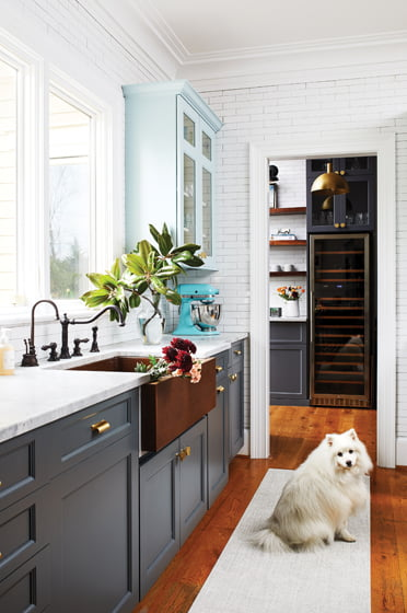 A copper farmhouse sink from Signature Hardware is a focal point.