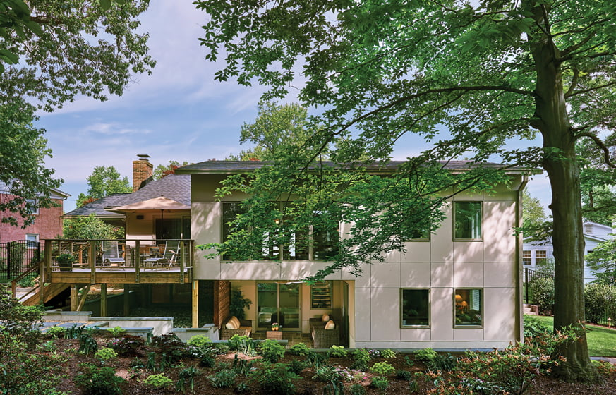 The addition includes an outdoor room tucked beneath a living area that opens onto the deck.