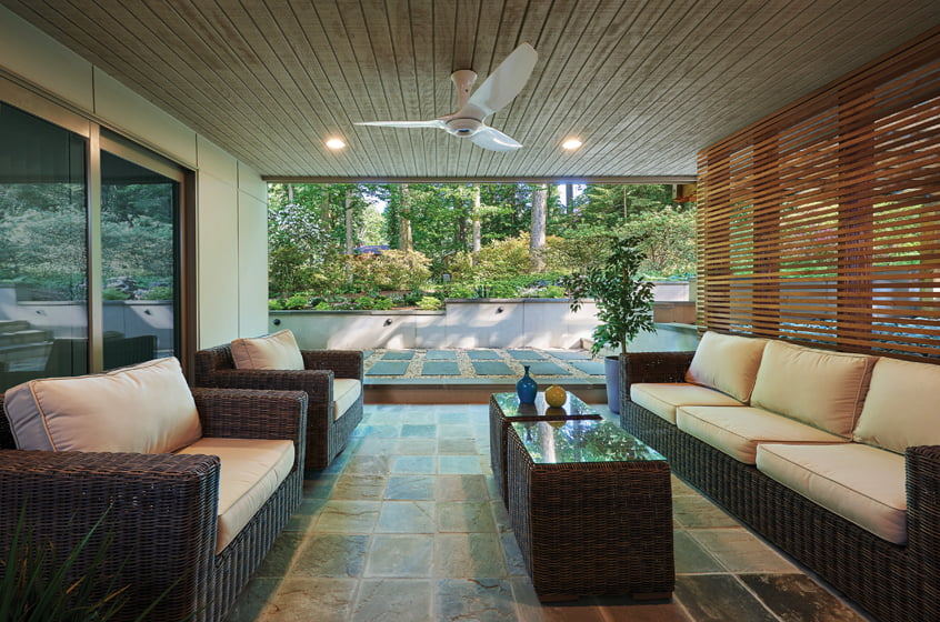 The outdoor room features a bluestone floor and a slatted-wood screen on one side.