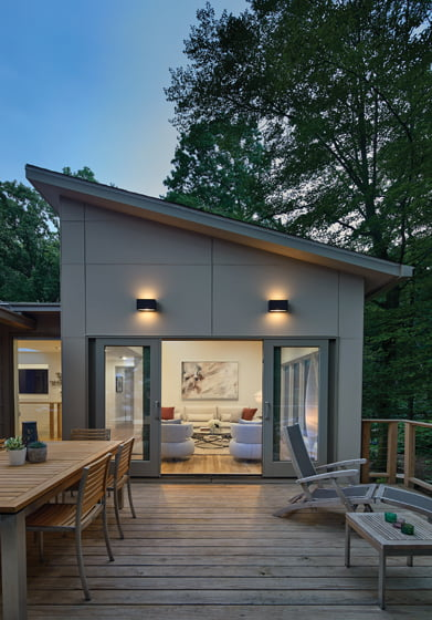 On the addition's second floor, the living area opens out to the deck via sliding-glass doors.
