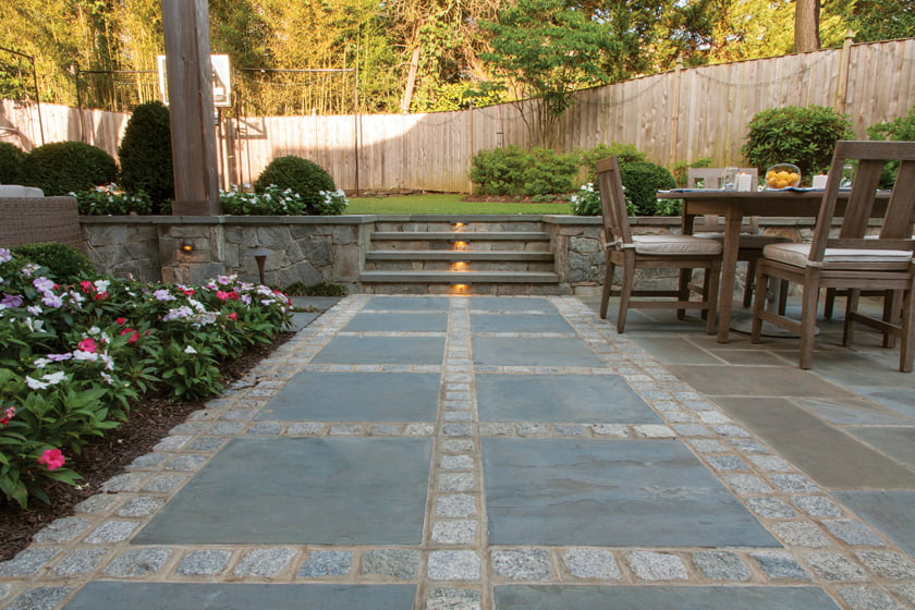 Flagstone pavers bordered by cobblestones form a path to the stairs, which lead up to the lawn and sport court.