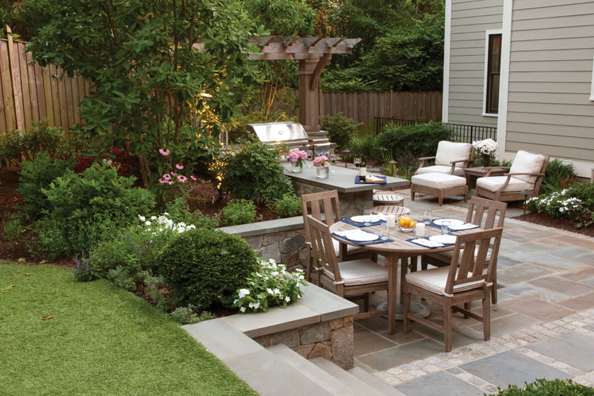 A retaining wall capped with Pennsylvania flagstone defines the eating area.
