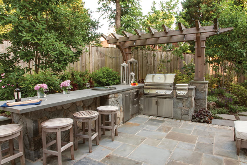 The outdoor kitchen features a flagstone countertop with space for bar seating and built-in appliances.
