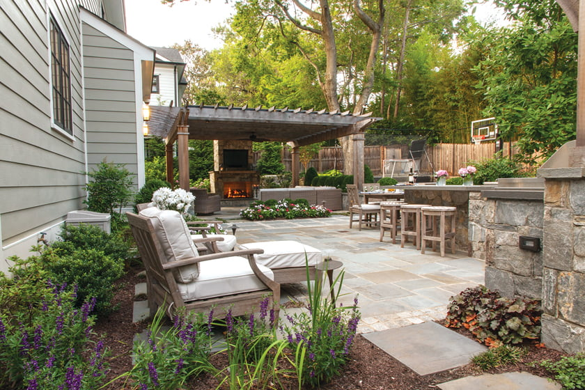 Pennsylvania flagstone paves the patio, which stretches from the outdoor kitchen, rimmed with May Night salvia and heuchera.