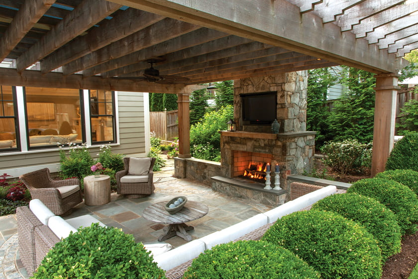 A Carderock stone fireplace offers a focal point in the seating space beneath a cedar pergola.