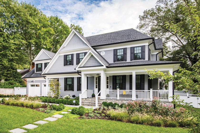 The traditional clapboard home features a wrap-around porch and the garage tucked off to the side.
