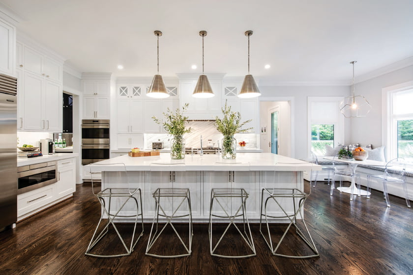Gabby stools pull up to the large kitchen island above which Visual Comfort pendants hang.
