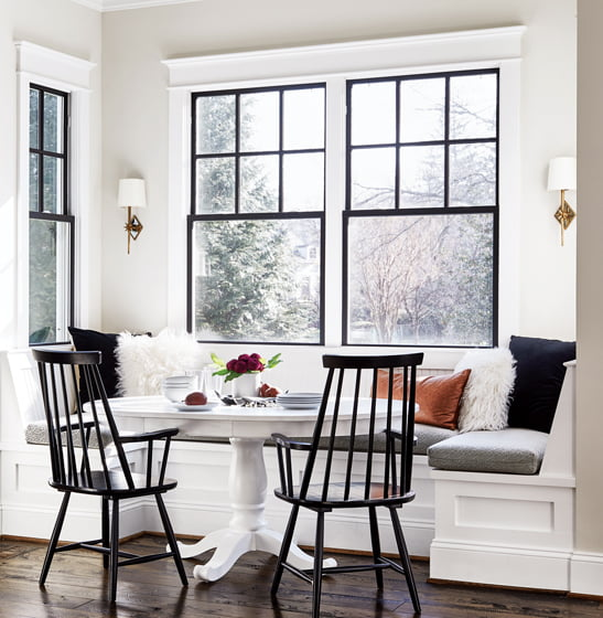 In the breakfast nook, an existing table was painted white and paired with black Windsor chairs.