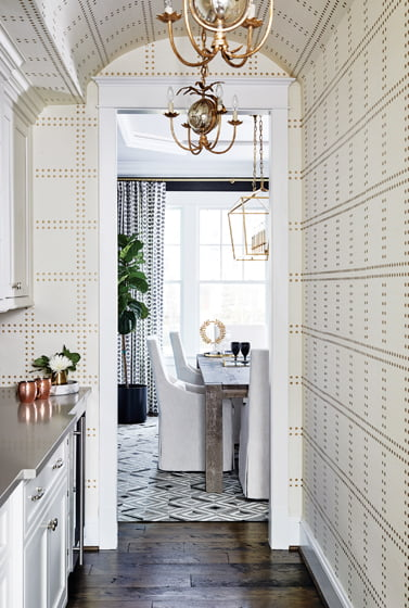 The butler's pantry sports Phillip Jeffries grass-cloth wallpaper and pendants from Visual Comfort.