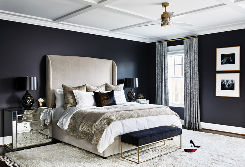 In the master bedroom, a bedstead by Looney & Sons Upholstery pairs with mirrored nightstands from Worlds Away.