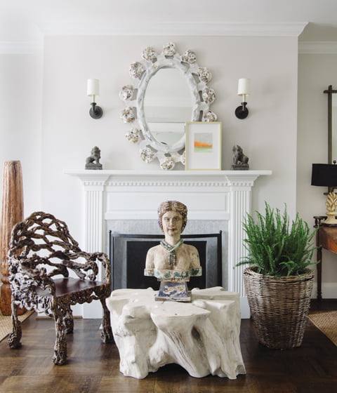 """Near a floating fireplace wall, a """"root"""" chair by J.F. Chen pulls up to a trunk table topped with an antique masthead."""
