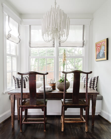 An Arteriors chandelier and antique Chinese chairs define the kitchen's eat-in nook.