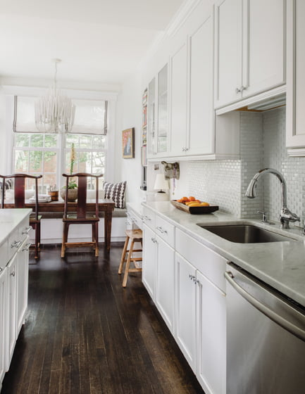 The galley kitchen features Carrara marble counters and a glass-tile backsplash.