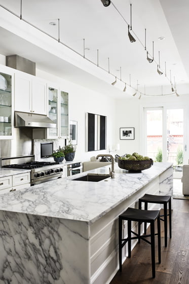 The kitchen's original dark-gray cabinetry was painted white and marble countertops were installed.