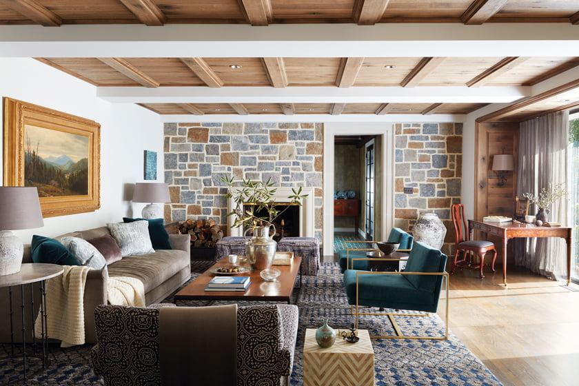 In the living room, Sutton added white-oak paneling and a stone wall with limestone trim around the fireplace.