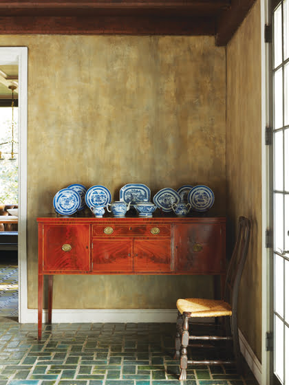 The owners' Delftware stands out against the dining room's shimmering glazed wall and existing tile floor.