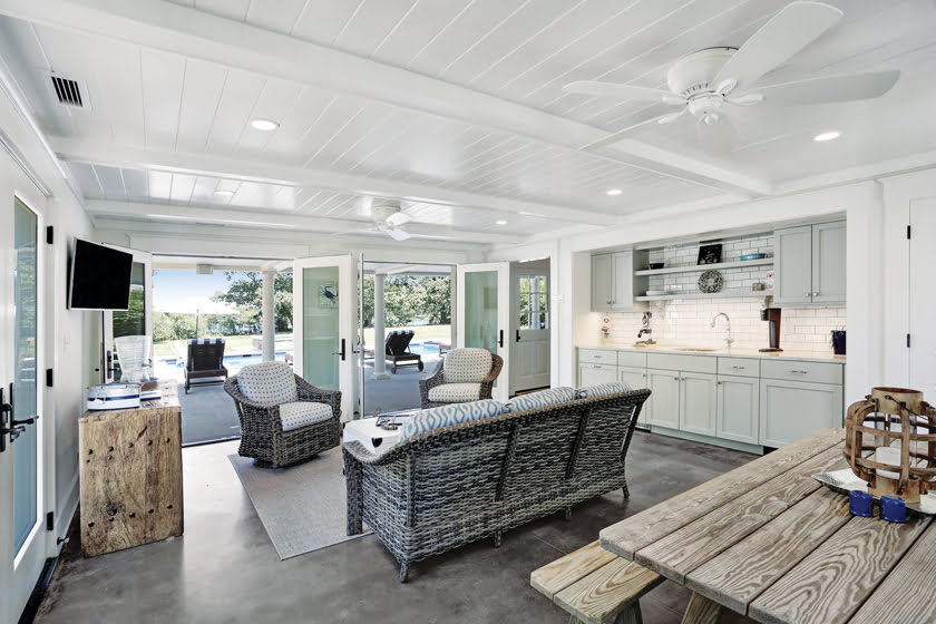 French doors connect the pool house great room to the outdoor gathering area.