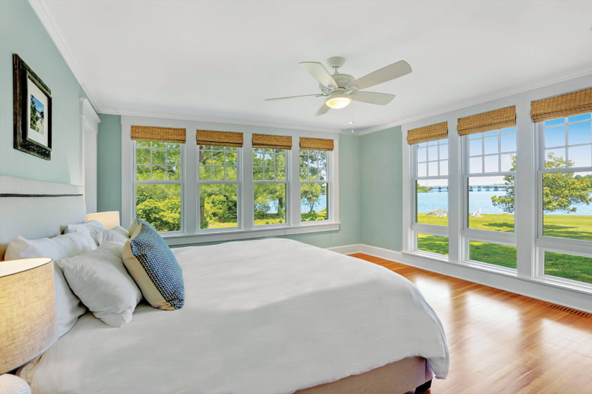 The serene master bedroom enjoys spectacular water views, thanks to two banks of Jeld-Wen windows.