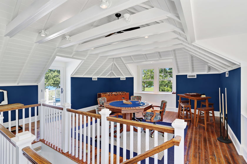 The former hayloft's original rafters and wood floors impart rustic charm in the upstairs game room.