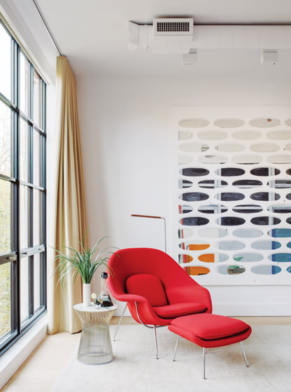 A Saarinen Womb Chair sits beside a painting by Jorge Macchi in the master bedroom.