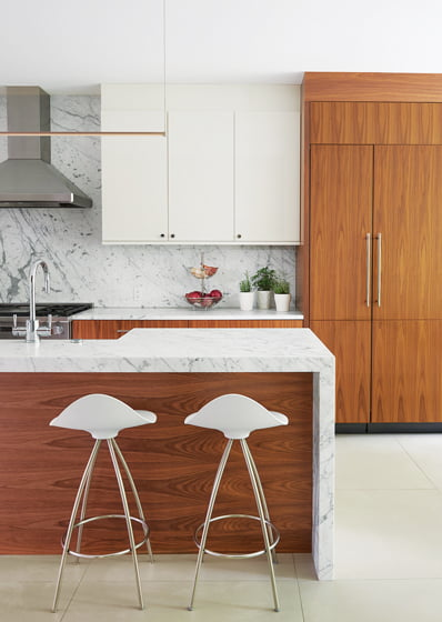 The minimalist kitchen juxtaposes white-lacquered and walnut Wood-Mode cabinetry; the countertop is statuary marble.