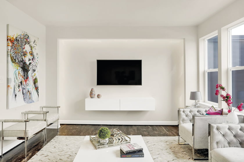 In the white-on-white family room, a dramatic accent wall is illuminated with dimmable lights. © Marcus Wilborn