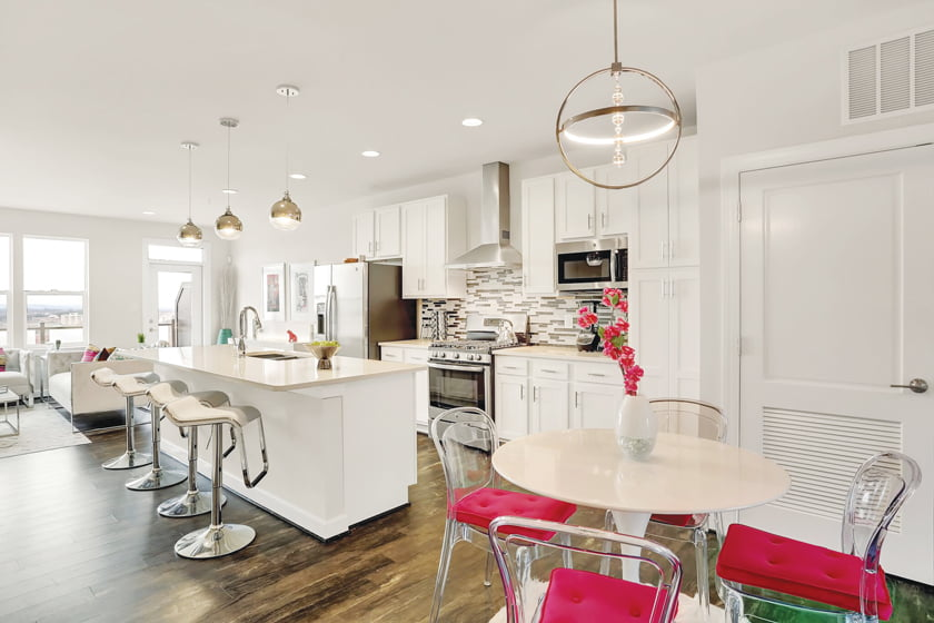 """Reynolds created a """"glam"""" look in a Sterling kitchen with glass-and-chrome pendants above the island. © Marcus Wilborn"""