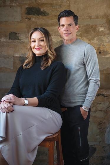 Sarita Simpson and Jason Claire pose in Thos. Moser's Georgetown showroom. © Michael Ventura.