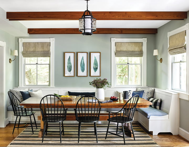 In a Chevy Chase farmhouse, a custom banquette and rustic table complement existing beams in the dining room.
