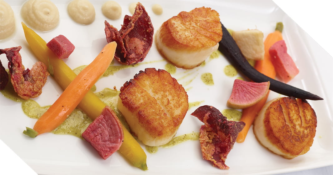 The new menu at Café Mezzanotte includes seared scallops with watermelon radish, rainbow carrots and beet chips. Photo: Tony J. Photography.