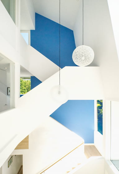 The tower's drywall stair creates a monolithic, sculptural effect; Moooi pendants hung in the entry add an airy quality.
