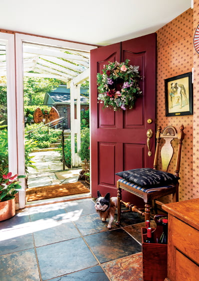 A burgundy-red door welcomes guests into the foyer.