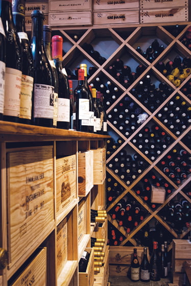 The adjacent cellar—one of two on the property—stores bottles on floor-to-ceiling shelves.