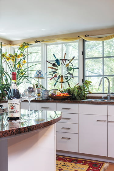 The kitchen, which has witnessed four makeovers, overlooks the greenery through a wide expanse of windows.