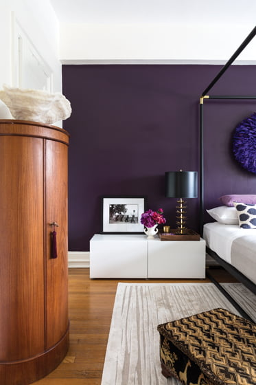 A curved, French Art Deco cabinet and Ikea nightstand reflect Dougan's eclectic design style.