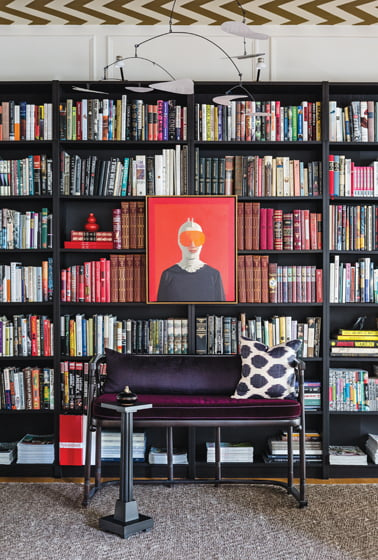 In the foyer, a painting by Vonn Cummings Sumner is mounted on Ikea bookcases that extend into the living room.