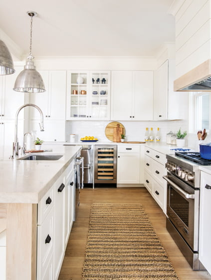 Shaker-style cabinets sourced at Kitchen Concepts in Annapolis line the white kitchen.
