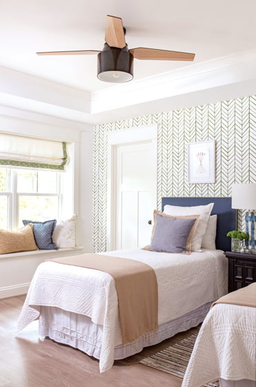 The lower-level guest room combines Serena & Lily wallpaper and custom shades with Samuel & Sons trim.